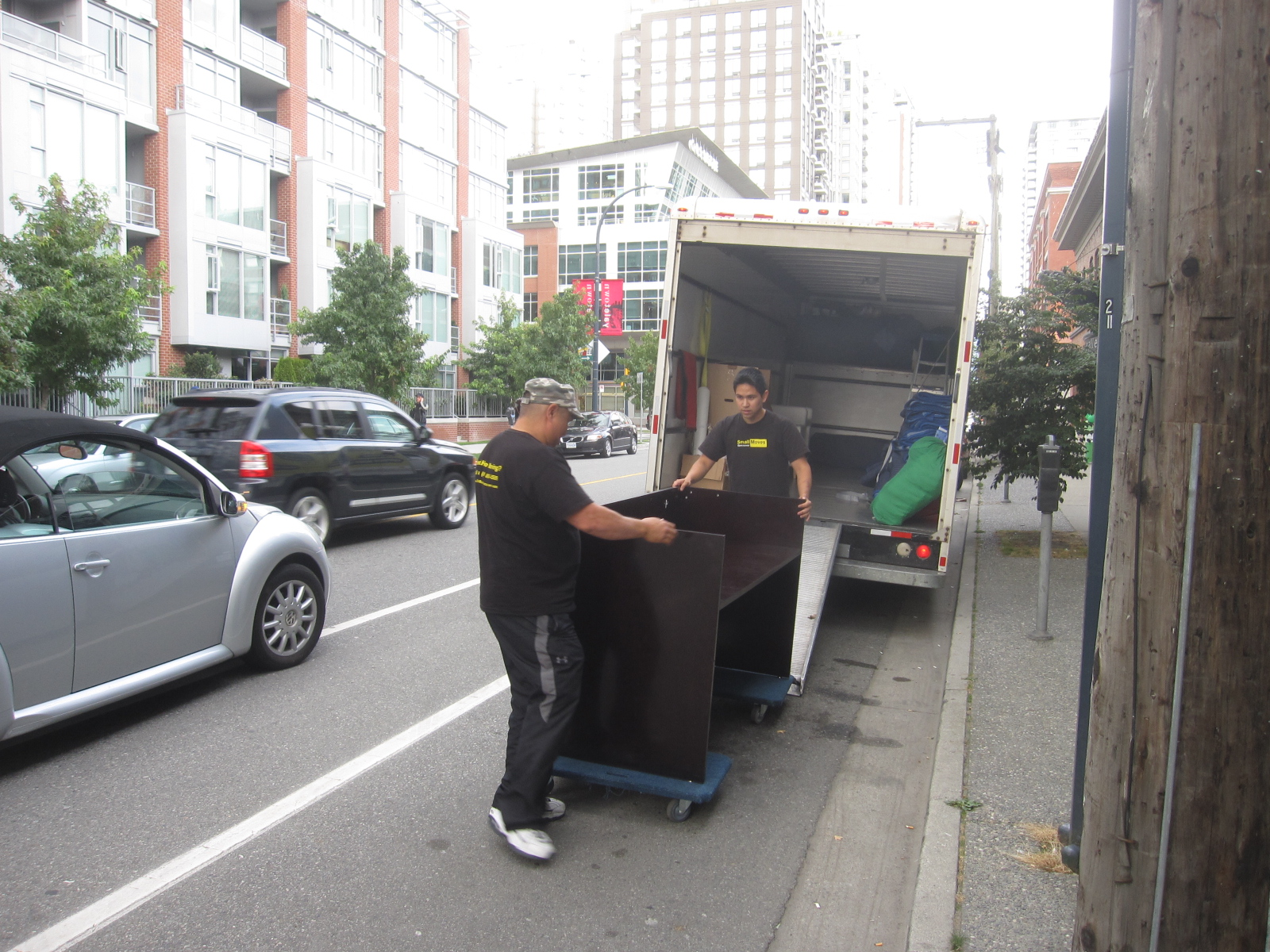 2 movers moving a desk into a 5 ton truck